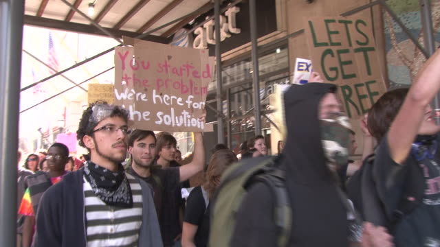 protesters holding signs and chanting, march down broadway during the height of the occupy wall street movement in lower manhattan. - occupy protests stock videos & royalty-free footage
