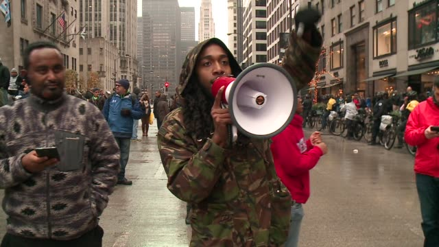 stockvideo's en b-roll-footage met wgn protesters holding up fists stand in the middle of michigan avenue on black friday in the wake of the release of the video showing the shooting... - chanten