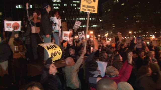 protesters holding up signs in street during occupy wall street movement audio / new york city, new york, united states - occupy protests stock videos & royalty-free footage