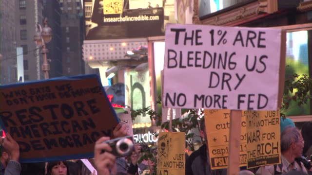 protesters holding up signs in time square during the occupy wall street movement audio / new york city new york united states - time's up social movement stock videos and b-roll footage