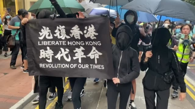 protesters in hong kong carry a flag reading 'liberate hong kong revolution of our times' as the city faces up to life under a new security law on... - hong kong flag stock videos & royalty-free footage