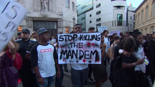 vídeos de stock, filmes e b-roll de protesters in london holding up signs and chanting stop killing the mandem in a display of solidarity for victims of police shootings in the usa - stop placa em inglês