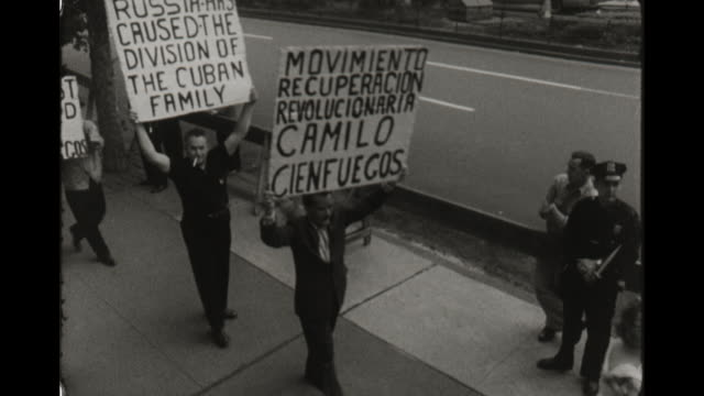 protesters in new york city protest the cuban sanctions and communism, carrying signs saying communists killed camilo cienfuegos. - 1960 stock videos & royalty-free footage