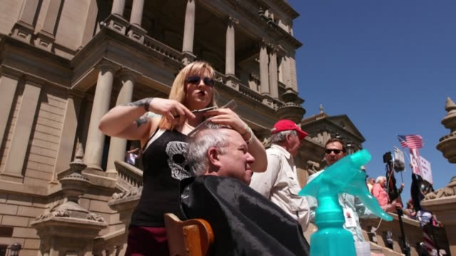 """protesters in the us state of michigan launch """"operation haircut"""", with barbers using their scissors and clippers outside the state capitol - lansing stock videos & royalty-free footage"""