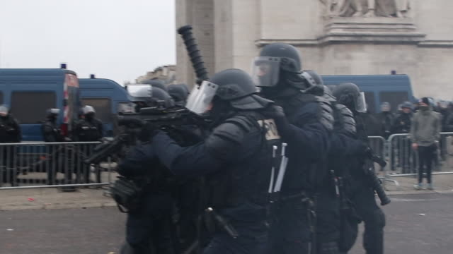 protesters in yellow vests in front of the triumphal arch with police and gendarmerie forces with a flash ball