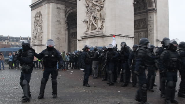 protesters in yellow vests in front of the triumphal arch with police and gendarmerie forces with a flash ball - 民主主義点の映像素材/bロール