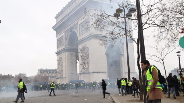 protesters in yellow vests in front of the triumphal arch with Tear gas
