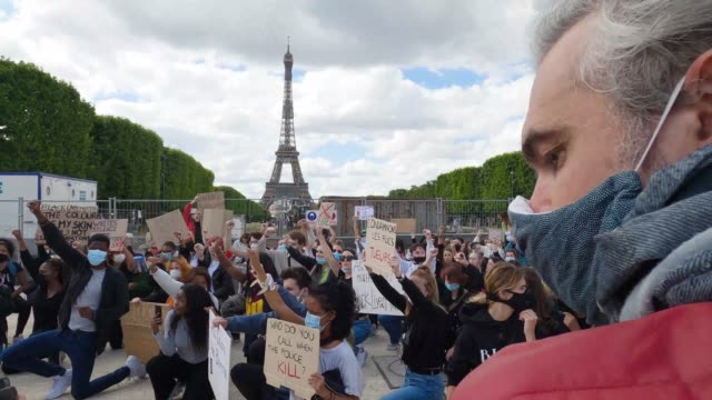 protesters kneel during a demonstration against racism and police brutality on the champs de mars in front of the eiffel tower on june 06, 2020 in... - ひざまずく点の映像素材/bロール