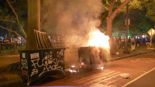stockvideo's en b-roll-footage met protesters light a dumpster on fire, hold signs and chant at the police. - afvalcontainer container