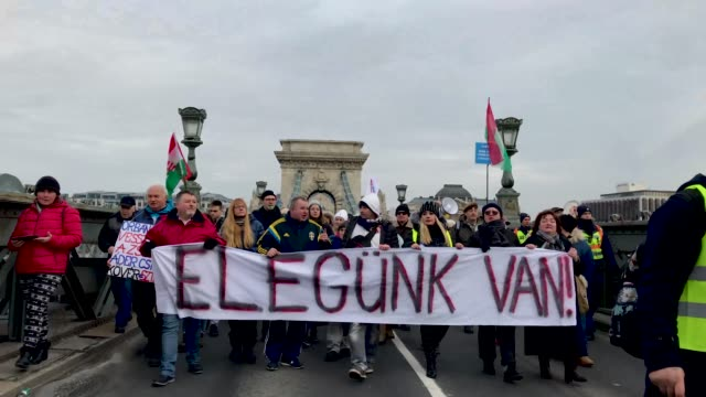 Protesters march across Budapest's famous Szechenyi Chain Bridge with a sign saying 'We Have Had Enough' during a demonstration against recent...