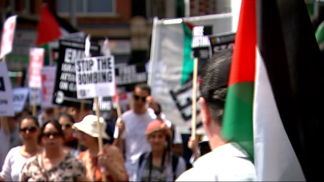 protesters march against israel's military action in gaza; england: london: ext various shots people marching with palestinian flags and placards... - palestinian stock videos & royalty-free footage