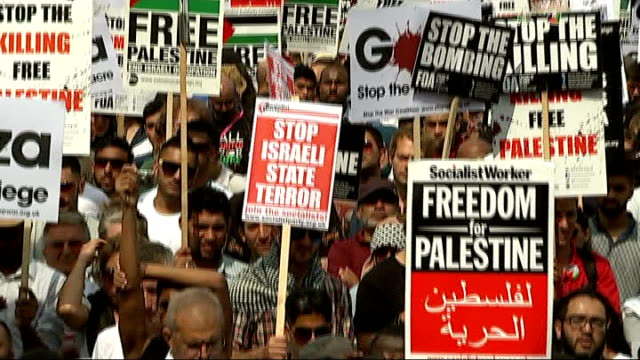 protesters march against israel's military action in gaza; england: london: tilt down crowd on street with placards listening to speaker - protestor stock videos & royalty-free footage
