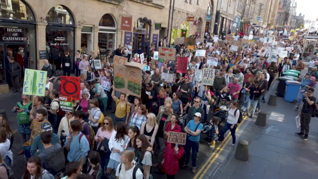 protesters march and hold placards as they attend the global climate strike on september 20, 2019 in edinburgh, scotland. millions of people are... - ストライキ点の映像素材/bロール