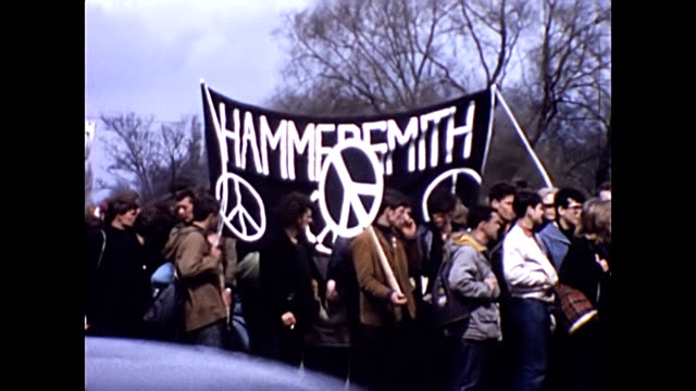 protesters march from aldermaston to london:- runnymede surrey / people march along the road with cars driving past. ban the bomb cnd banners... - rebellion stock videos & royalty-free footage