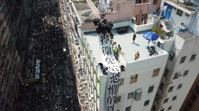 protesters march from causeway bay towards wan chai on the 70th anniversary of china the day saw some of most violence since the protests began - wan chai stock videos & royalty-free footage