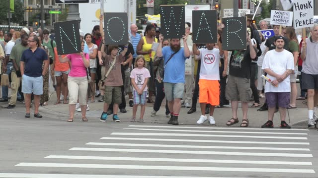 / protesters march through downtown against military action in syria by the united states / marchers cross at a pedestrian crosswalk into oncoming... - peace demonstration stock videos and b-roll footage