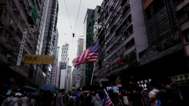 protesters march through the streets carrying an american flag in hong kong, china. - hong kong flag stock videos & royalty-free footage