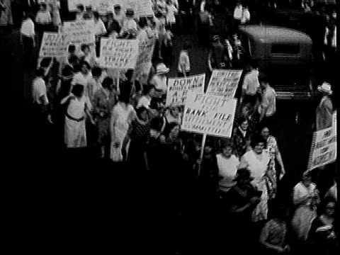 protesters marching along city street with placards / large crowd gathered in street labor protest on january 01 1932 in allentown pennsylvania - anno 1932 video stock e b–roll