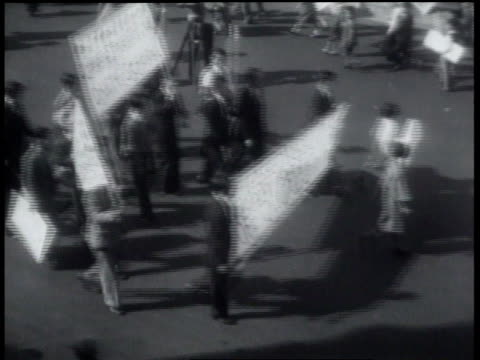 vidéos et rushes de protesters marching with banners / protesters walking through city streets / protesters waving american flags - 1931