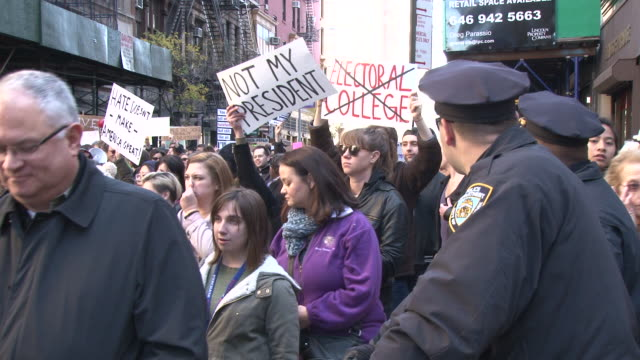 protesters move out of union square through the saturday farmer's market and begin their march toward trump towers in midtown / police temporarily... - us republican party 2016 presidential candidate stock videos & royalty-free footage
