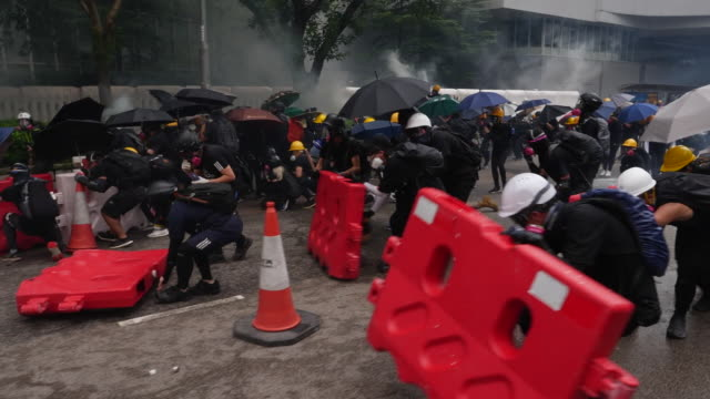 protesters moving forward behind makeshift barricades in hong kong - demonstrant stock-videos und b-roll-filmmaterial