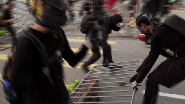 protesters moving part of a fence to create a makeshift barricade in hong kong - dragging stock videos & royalty-free footage