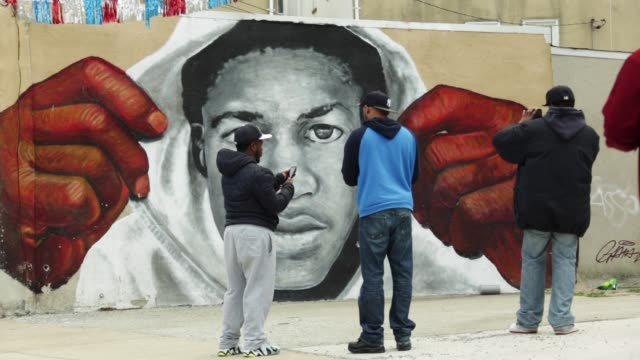 vidéos et rushes de protesters pass by a wall painting of trayvon martin during a march from the western district police station to the city hall in honor of freddie... - baltimore