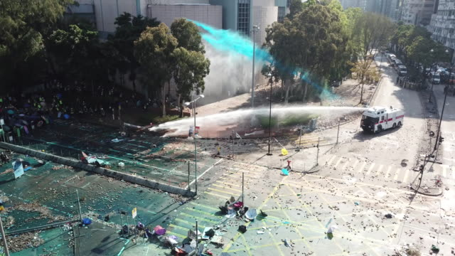 protesters prepared defences and blocked roads around hong kong polytechnic university in hung hom. police fired tear gas and water cannon. - 放水砲点の映像素材/bロール
