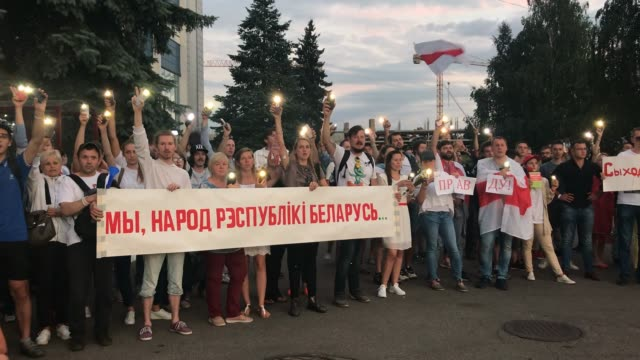 protesters put on their flash lights of their phones as they wave flags and hold a banner demonstrating outside belorussian state tv headquarters on... - belarus stock videos & royalty-free footage