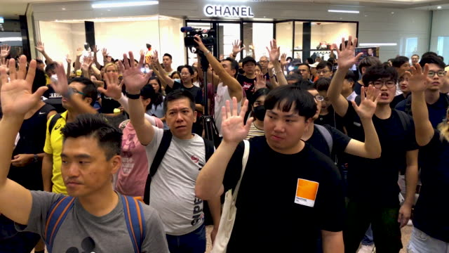 "protesters raise their hands as they sing the glory to hong kong protest ""anthem"" during a demonstration in times square shopping mall on september... - times square causeway bay stock videos & royalty-free footage"