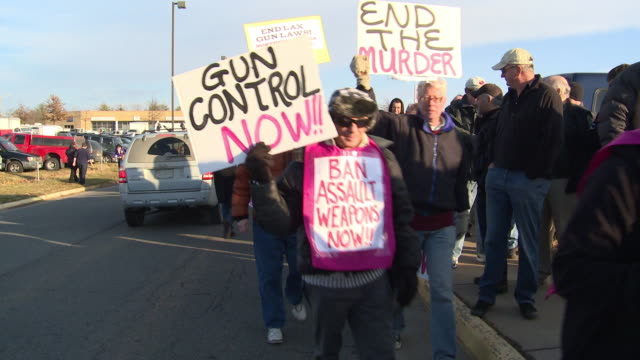 protesters rally against private gun sales at the nation's gun show at the dulles expo center on december 28, 2012 in dulles, virginia - 全米ライフル協会点の映像素材/bロール