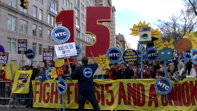 protesters rallying and chanting in columbus circle demanding that the minimum wage in the united states is raised to a livable $15 an hour. - gewerkschaft stock-videos und b-roll-filmmaterial