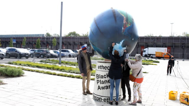 Protesters roll out their banners in front of the main entrance to the event German automaker Volkswagen AG annual shareholders' meeting on May 14...