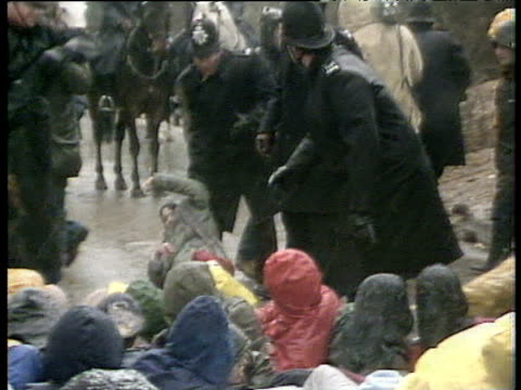 protesters sitting and lying in road some being moved or carried by police greenham common protests 31 mar 83 - 住宅問題点の映像素材/bロール