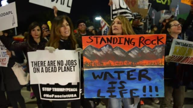 protesters stage a demonstration against us president donald trump in los angeles, california, usa on january 24, 2017. us president donald trump... - nordamerikansk indiankultur bildbanksvideor och videomaterial från bakom kulisserna