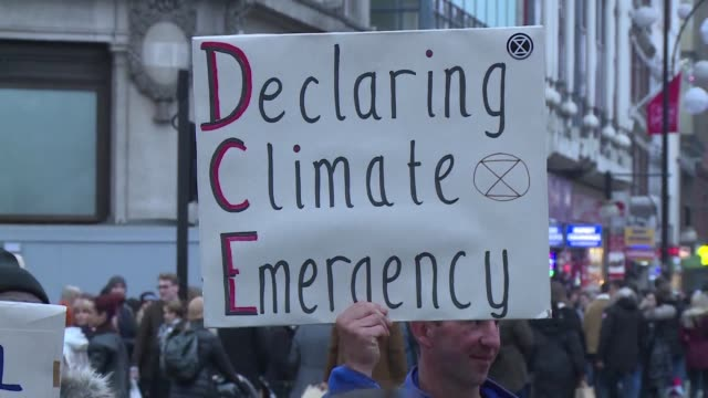 protesters taking part in what they call the extinction rebellion take part in their latest direct action blocking traffic at london shopping mecca... - servizio segmento produzioni video stock e b–roll