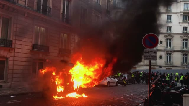 Protesters taunt police behind a burning car during the 'yellow vests' demonstration near the Arc de Triomphe on December 8 2018 in Paris France...