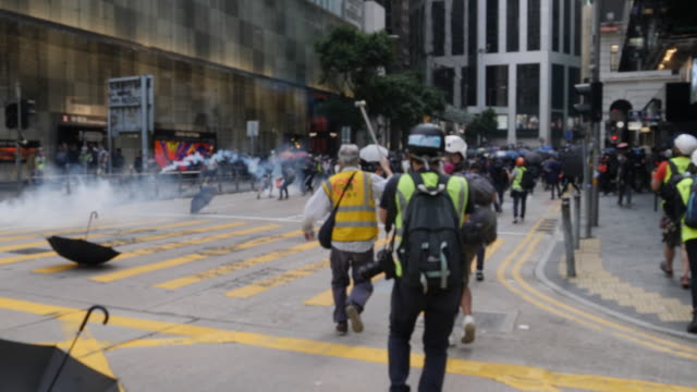 protesters to over the streets in central hong kong blocking roads and lighting fires police shot tear gas and made many arrests - central district hong kong stock videos & royalty-free footage