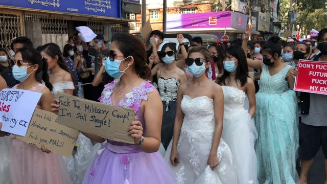 protesters wearing bridal costumes shout slogans and hold placards during an anti-coup rally on february 10 in yangon, myanmar. myanmar declared... - ミャンマー点の映像素材/bロール