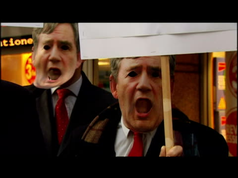 vídeos y material grabado en eventos de stock de protesters wearing gordon brown masks opposing proposed labour cuts to local government budgets and vat levels - iva