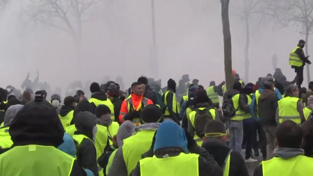 vídeos de stock, filmes e b-roll de protesters wearing yellow vests clash with riot police during a demonstration over high fuel prices on the champs elysee in paris france on december... - vest
