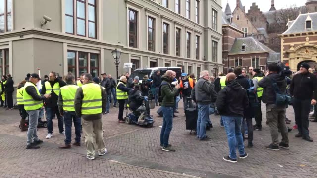 vídeos de stock, filmes e b-roll de protesters wearing yellow vests stage a demonstration against rising oil prices and living costs outside the parliament building in the hague... - vest
