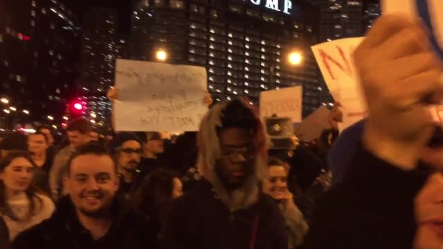 protesters with anti-trump signs march through the streets of downtown chicago in protest of trump's election to the presidency. - president stock videos & royalty-free footage