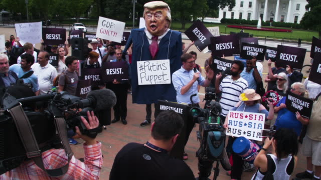 protesters with papier mache trump doll labeled putin's puppet gather outside of white house - papier 個影片檔及 b 捲影像