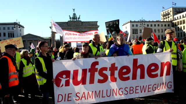 """protesters with the banner """"stand up"""" - the collection movement"""" in front of the brandenburg gate.supporters of the new left-wing """"stand up"""" movement... - links platz stock-videos und b-roll-filmmaterial"""