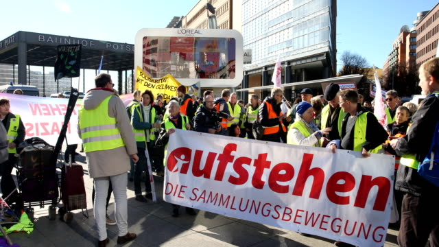 """protesters with the banner """"stand up"""" - the collection movement"""" . supporters of the new left-wing """"stand up"""" movement gather at a demonstration at... - links platz stock-videos und b-roll-filmmaterial"""
