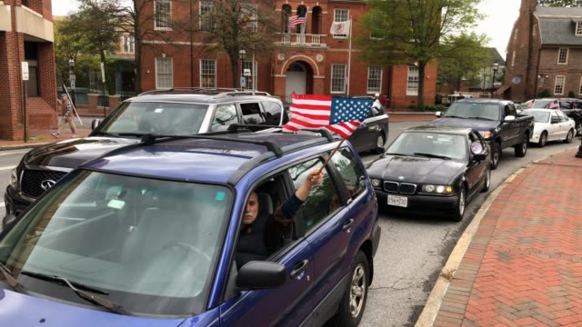 "protesters with the group ""reopen maryland"" wave and american flag and honk the horns of their cars as they rally near the state house to call on the... - maryland us state stock videos & royalty-free footage"