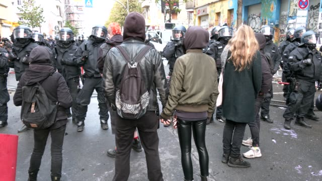 protesting couple face police officers outside liebigstrasse 34, also known as liebig34, during the eviction of its residents on october 09, 2020 in... - links platz stock-videos und b-roll-filmmaterial