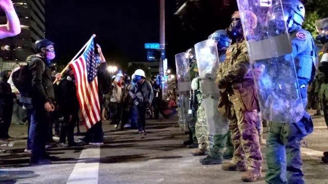 protestor holds an american flag in front of federal officers on july 29, 2020 in portland, oregon. protests against the federal presence in portland... - portland oregon stock videos & royalty-free footage