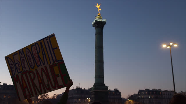 protestor holds up a sign as protesters demonstrate against the french government's global security act as thousands take to place de la bastille on... - バスティーユ点の映像素材/bロール